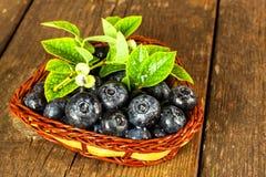 Myrtilles humides dans un petit panier en osier La forêt fraîchement sélectionnée porte des fruits sur une table en bois Ventes d Photographie stock libre de droits