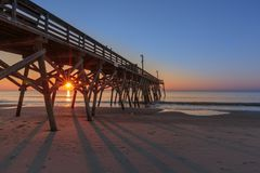 Myrtle Beach Pier at Sunrise. First light of the sun peeking through the pier at Myrtle Beach stock photo