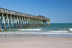 Myrtle Beach, South Carolina State Park Fishing Pier. Fishing pier with calm seas and a clear sky with the beach in the foreground Royalty Free Stock Image