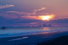 Myrtle Beach at sunset with pier and buildings in silhoette. Myrtle Beach at sunset with pier and buildings in silhouette. Featuring a cool blue ocean and warm Royalty Free Stock Image