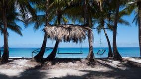 Mysig hängmatta och gunga som binds till palmträd bredvid förbluffa i Maldiverna arkivfoto
