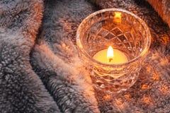 Mysig och mjuk vinterbakgrund, stearinljus på en filt Arkivfoto