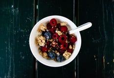 Mysli, lösa bär och yoghurtfrukost på det vita bunkeöverkantskottet med svart träbakgrund arkivfoton