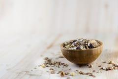 Mysli och granola i suddig träbakgrund (Grund öppning påtänkt för den estetiska kvaliteten av suddigheten) fotografering för bildbyråer