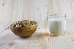 Myslit granola och mjölkar i suddig träbakgrund (Grund öppning påtänkt för den estetiska kvaliteten av suddigheten) royaltyfri bild