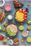 Myslit havreflingor, jordgubbar, kiwi, mjölkar, muttrar, physalisen, kaffe, bakelser Färgrik omväxlande frukost på en trägräsplan royaltyfri fotografi