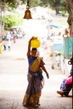 Mysore, India - June 27, 2018: Woman carrying a bowl of water. On her head stock image