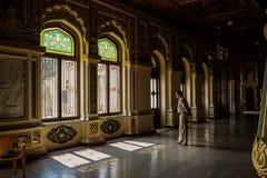 Mysore, Indien - 10. Dezember 2017: Verzierte Fenster von Mysore-Palast mit Schatten und Wachmann Lizenzfreies Stockbild