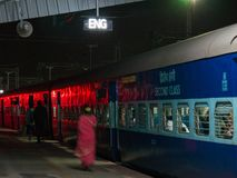 Passengers are heading for their wagon before the departure of the night train to Mysore. stock photos