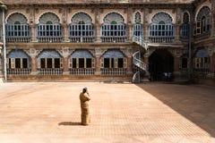 Mysore, la India - 10 de diciembre de 2017: Yarda en el palacio de Mysore con las ventanas y arcos con seguridad femenina Foto de archivo
