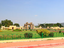 Mysore Palace gate. Mysore Palace grounds have many outbuildings and ancient walls plus temples gopurams pagodas and gates and caravans and carriages in the huge Stock Image
