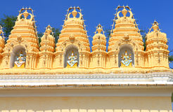 Mysore Palace gate. Mysore Palace grounds have many outbuildings and ancient walls plus temples gopurams pagodas and gates and caravans and carriages in the huge Stock Photos