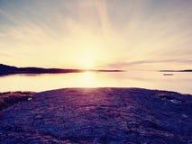 Mystères d'aube Lever de soleil de mer au-dessus de la côte, niveau d'eau silencieux Ciel bleu clair i Images stock