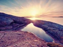 Mystères d'aube Lever de soleil de mer au-dessus de la côte, niveau d'eau silencieux Ciel bleu clair i Photos stock