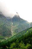 Mysteriöse, einsame Bergspitze umgeben durch Wald Stockfoto