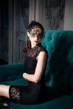 Mysteriöse Frau in der venetianischen Karnevalsmaske, die im Sofa im Innenraum sitzt Lizenzfreies Stockbild