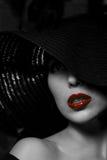 Mysteriöse Frau im schwarzen Hut. Rote Lippen Lizenzfreies Stockbild