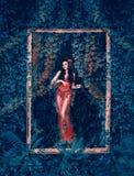 Mysteriöse Göttin des Waldes und der Natur kommt aus ihren Garten im schicken roten Kleid mit langem transparentem Zug und Blumen lizenzfreies stockbild