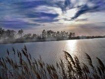 Mysteriöse Landschaft des Seeufers und des fabelhaften Himmels stockfoto