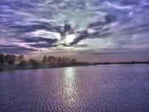 Mysteriöse Landschaft des Seeufers und des fabelhaften Himmels stockfotografie