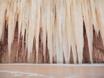 Mysteriöse riesige Eiszapfen in der sandigen Höhle nahe dem gefrorenen Wintersee Stockfotografie