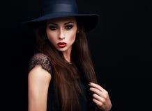 Mysteriöser Hut der Make-upfrau in Mode, der auf bla ausdrucksvoll schaut stockbild