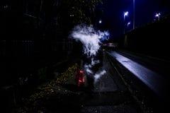 Mysteriöser Mann, der vaping Rauch ausatmet, der sein Gesicht beim Gehen auf die Straße während der Nachtzeit versteckt lizenzfreies stockbild