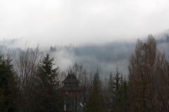 Mysteriöser Nebel über Gebirgswalddorf lizenzfreie stockfotos