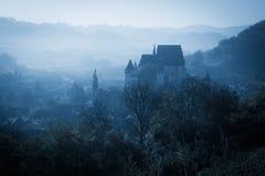 Mysteriöser nebelhafter Morgen über Biertan-Dorf, Siebenbürgen, Rumänien Lizenzfreies Stockfoto