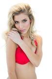 Mysteriöses attraktives blondes Modell im roten Bikini, der Kamera betrachtet Stockfoto
