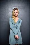 Mysteriöses blondes Mädchen auf einem grauen Wandhintergrund Stockfoto