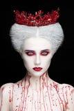 Mysteriöses Schönheitsporträt der Schneekönigin bedeckt mit Blut Helles Luxusmake-up Weiße Dämonaugen stockfotos