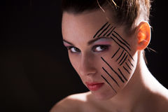 Mysterieus beauty. Beautiful woman with striped makeup on dark background Stock Image