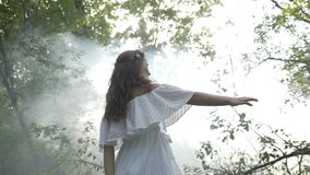 Mysterious angelic girl in white dress spinning amongst the trees in the forest -. Mysterious angelic girl in white dress spinning amongst the trees in the stock footage