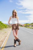 Mysterious attractive woman posing while hitchhiking. On a deserted road in summertime Stock Photography