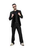 Mysterious bearded man in black suit and white sneakers holding collar. Full body length portrait isolated over white studio background Royalty Free Stock Photography