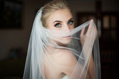 Mysterious beautiful blue eyes blonde bride hiding Royalty Free Stock Images