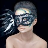 Mysterious beautiful girl in a black mask with feathers with green creative makeup in the studio on a dark background isolated Stock Photos