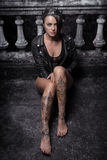 Mysterious beautiful woman with henna tattoo on legs. Mysterious beautiful woman in black bodysuit, leather jacket and crown with henna tattoo on her legs stock photography