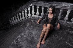 Mysterious beautiful woman with henna tattoo on legs. Mysterious beautiful woman in black bodysuit, leather jacket and crown with henna tattoo on her legs Stock Image