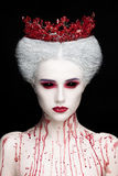 Mysterious beauty portrait of snow queen covered with blood. Bright luxury makeup. Black demon eyes. stock photos