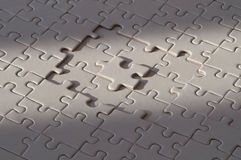 Mysterious Blank Puzzle. Photo of a blank puzzle with focused lighting. One of the parts is standing in the middle of other missing parts Royalty Free Stock Photos