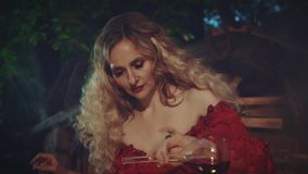 Mysterious blond woman in a red baroque dress with bare shoulders and lace. stock video footage