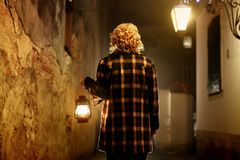 Mysterious blonde woman in elegant retro coat with old oil lantern walking in old French street in