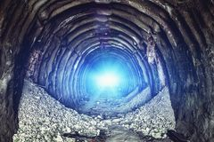 Mysterious blue light in the end of old round industrial tunnel or underground mine corridor stock photo