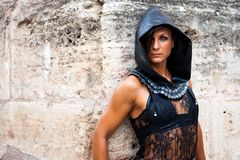 Mysterious brunette woman with leather hood looks at camera from the corner of a stone wall royalty free stock photography