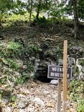 A mysterious cave entrance leading underground with a sign beside it that warns to not enter in spanish and english. stock photo