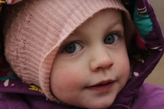 Mysterious deep eyes baby. Mysterious deep eyes of a small child in a hooded hat royalty free stock photography