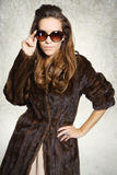 Mysterious elegant woman in a fur coat and sunglasses Stock Image