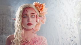 Mysterious elf girl. Creative pink makeup. Elvish ears. Free space on the right stock photo